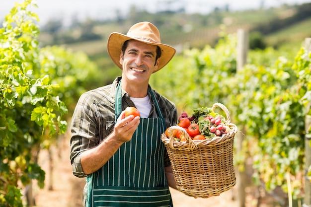 Portrait d'agriculteur heureux tenant un panier de légumes