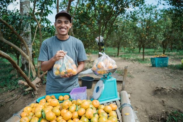 Portrait d'agriculteur heureux vendant des fruits orange avec sac en plastique