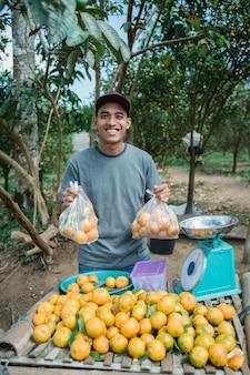 Portrait d'agriculteur heureux vendant des fruits orange