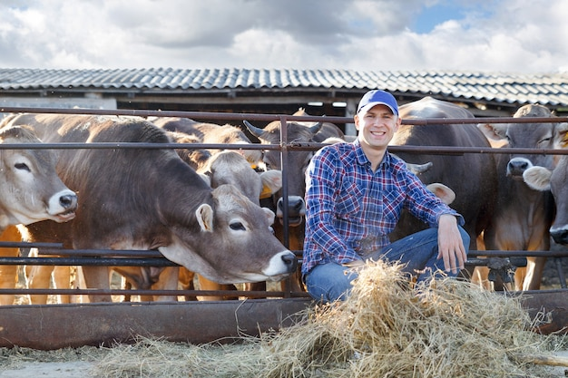 Portrait d'un agriculteur de sexe masculin positif dans une ferme près de vaches