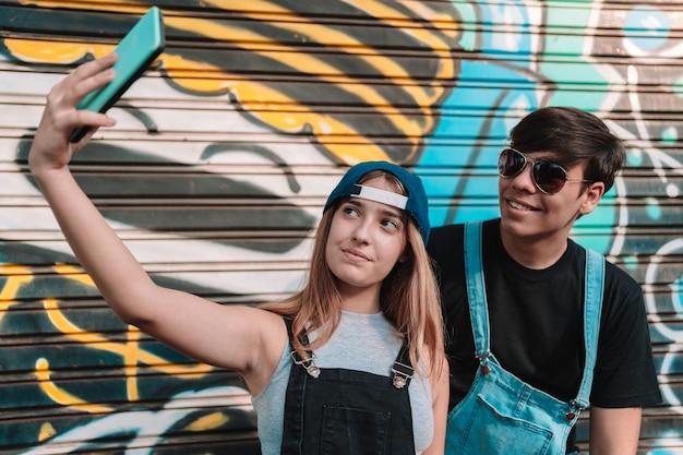 Portrait d'amis adolescents prenant un selfie sur une porte peinte.