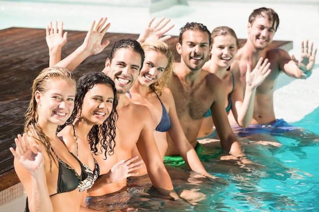 Portrait d'amis agitant les mains dans la piscine