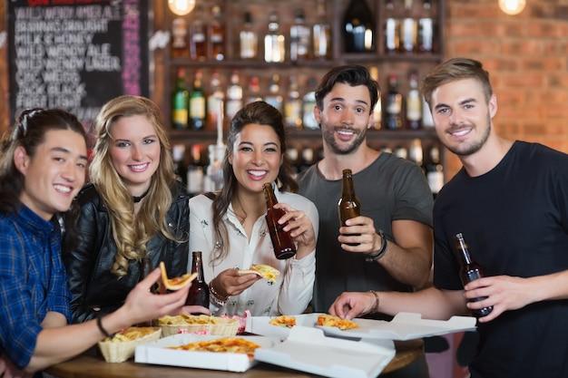 Portrait d'amis ayant une pizza avec de la bière