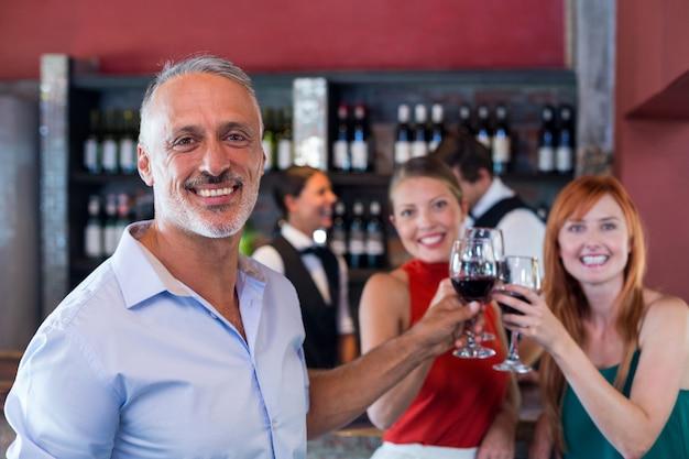 Portrait d'amis grillage avec un verre de vin rouge dans un bar