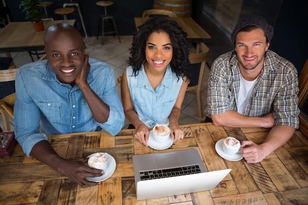 Portrait d'amis heureux prenant un café avec un ordinateur portable sur une table en bois au café