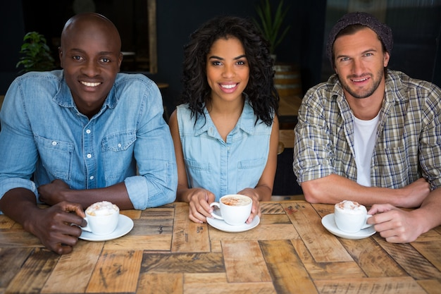 Portrait d'amis heureux prenant un café à table en bois au café