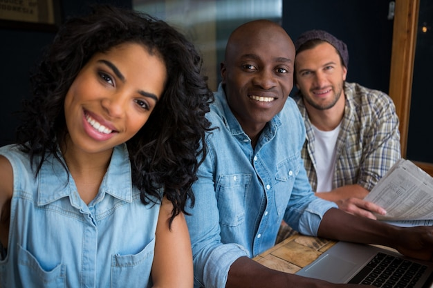 Portrait d'amis heureux à table dans un café