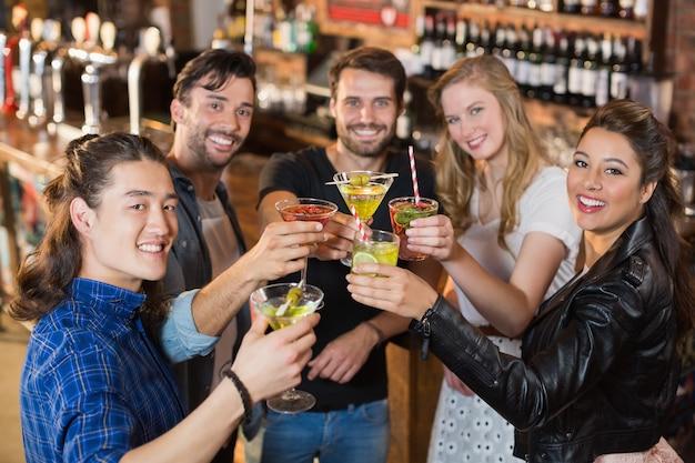 Portrait d'amis heureux tenant des boissons en se tenant debout dans le bar