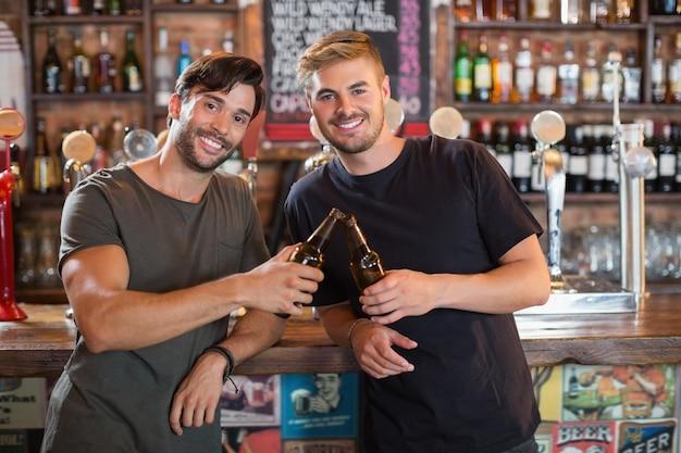 Portrait d'amis masculins souriants, grillage des bouteilles de bière