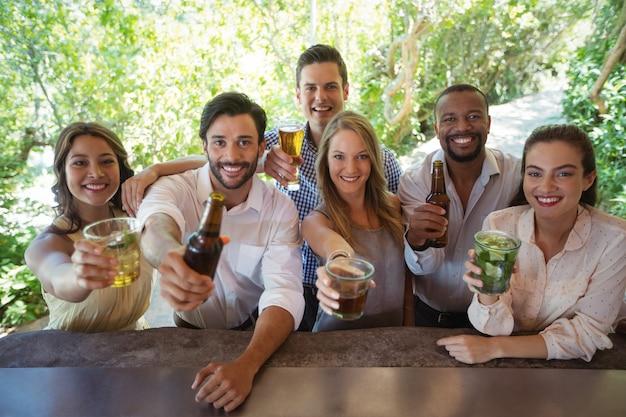 Portrait d'amis souriants montrant de l'alcool au comptoir
