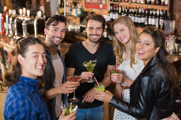 Portrait d'amis souriants tenant des boissons en se tenant debout dans le bar
