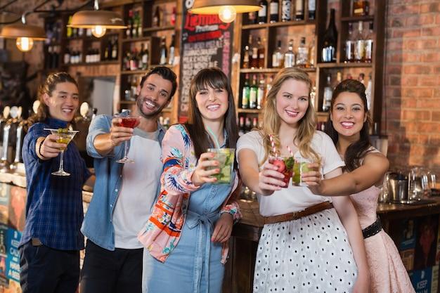 Portrait d'amis souriants tenant des boissons