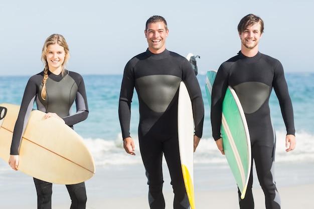 Portrait d'amis surfeurs avec planche de surf debout sur la plage