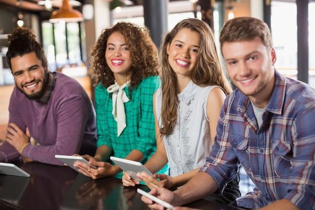 Portrait d'amis tenant des tablettes numériques au restaurant