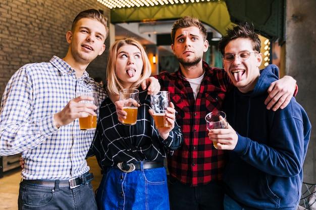 Portrait d'amis tenant les verres de bière