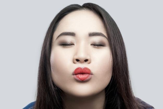 Portrait d'amoureuse belle brune asiatique jeune femme en veste en jean bleu décontractée avec maquillage debout les yeux fermés et envoyant un baiser. tourné en studio intérieur, isolé sur fond gris clair.