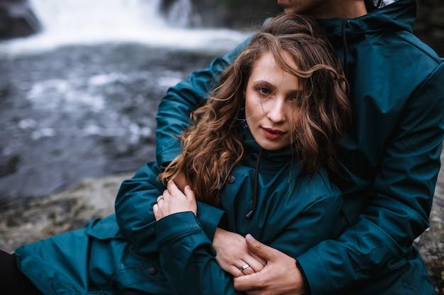 Portrait d'amoureux en imperméables verts, assis sur une pierre, contre une cascade