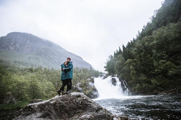 Portrait d'amoureux en imperméables verts, debout sur une pierre, contre une cascade