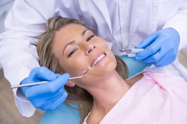 Portrait d'angle élevé de femme par l'outil de moulage de dentiste