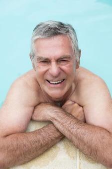 Portrait d'angle élevé d'heureux homme senior nageant dans la piscine