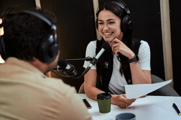 Portrait d'une animatrice de radio heureuse souriante écoutant un présentateur invité masculin et tenant un script