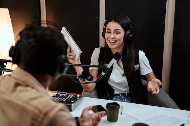 Portrait d'une animatrice de radio heureuse en train de rire en écoutant le présentateur invité masculin et en tenant un script