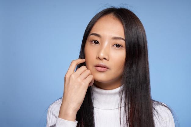 Portrait d'apparence asiatique de femme sur le modèle de pull blanc bleu.
