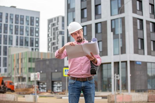 Portrait d'architecte au travail avec casque dans un chantier de construction, lit le plan, projets papier