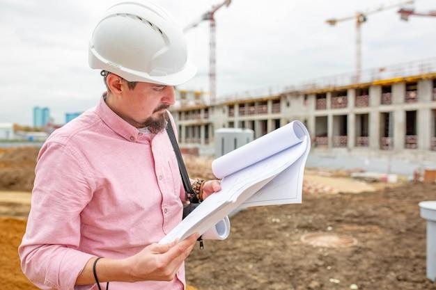 Portrait d'architecte au travail avec casque dans un chantier de construction, lit le plan.