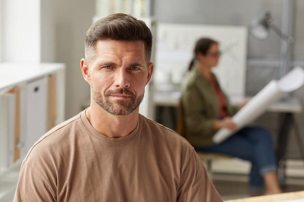 Portrait d'architecte barbu mature à la caméra et souriant alors qu'il était assis au bureau de dessin au soleil,