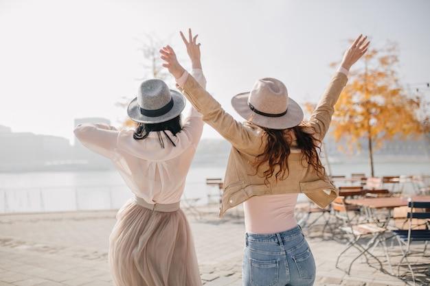 Portrait de l'arrière de deux dames excitées exprimant des émotions positives appréciant la vue sur la rivière