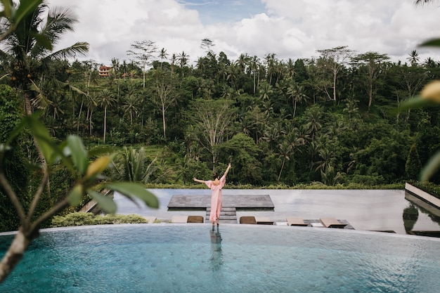 Portrait de l'arrière du modèle féminin en robe rose regardant la forêt tropicale. tir extérieur d'une femme gracieuse dansant près de la piscine.