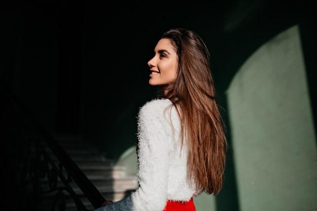 Portrait de l'arrière de la fascinante femme aux cheveux longs debout dans le noir