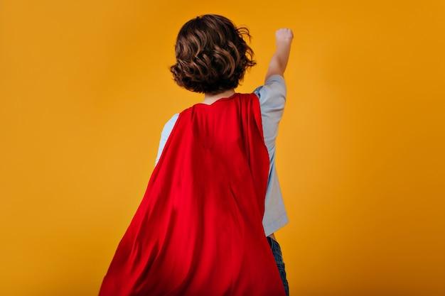Portrait de l'arrière de la supergirl avec une coiffure courte