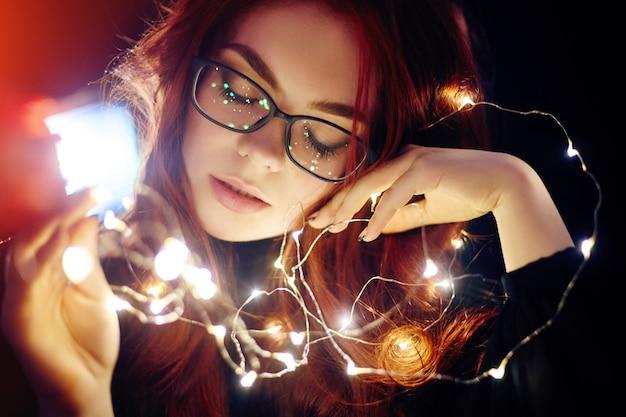 Portrait d'art d'une femme aux cheveux rouges dans les lumières de noël.