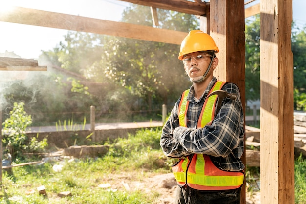 Portrait d'un artisan asiatique tenant un marteau dans les mains, debout dans un atelier spacieux et regardant la caméra sur un chantier de construction.