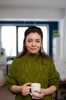 Portrait d'un artiste designer souriant à la caméra tenant une tasse de café