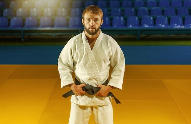 Portrait d'artiste martial en kimono blanc avec ceinture noire indoor