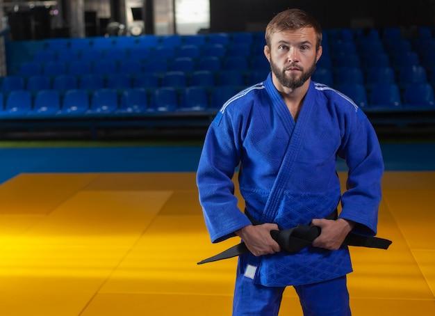 Portrait d'artiste martial en kimono bleu avec ceinture noire intérieure
