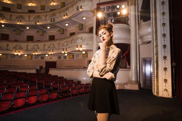 Portrait de l'artiste mime féminin réfléchie debout sur scène