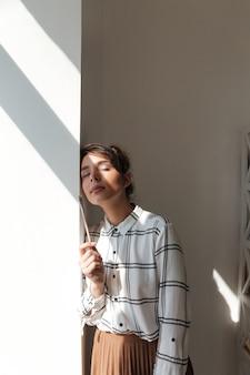 Portrait d'une artiste souriante tenant un pinceau et posant