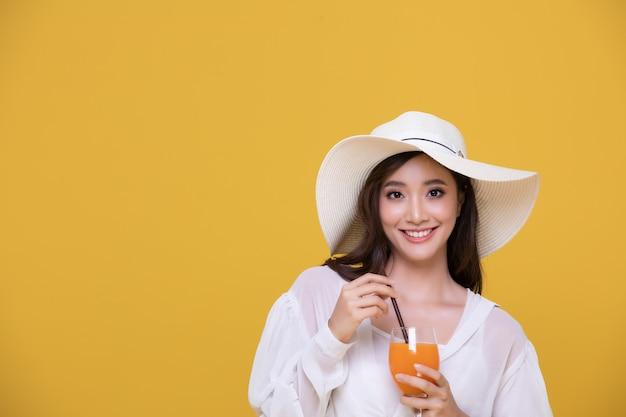 Portrait asiatique belle jeune femme heureuse avec un chapeau souriant gai et tenant un verre de jus d'orange en été et en regardant la caméra isolée sur fond de studio jaune.