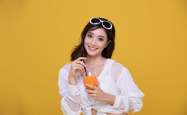 Portrait asiatique belle jeune femme heureuse avec des lunettes de soleil souriant gai et tenant un verre de jus d'orange en été et regardant la caméra isolée sur fond de studio jaune.