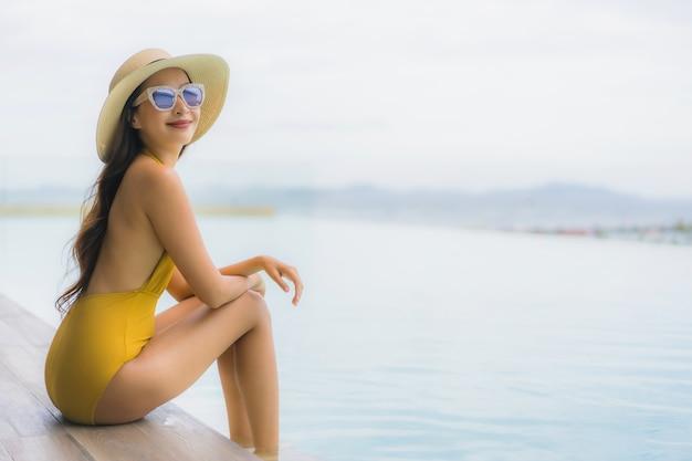 Portrait asiatique belle jeune femme heureuse sourire se détendre autour d'une piscine extérieure en vacances