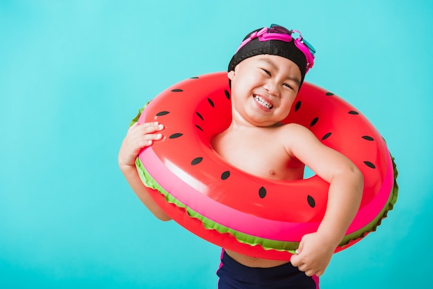 Portrait asiatique heureux mignon petit enfant garçon porter des lunettes et un maillot de bain tenir bague gonflable pastèque