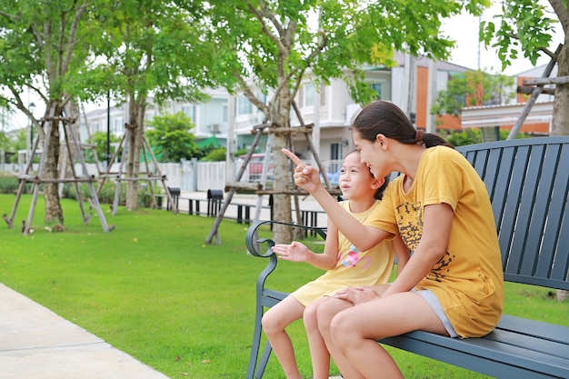 Portrait asiatique mère et fille de détente assis sur un banc dans le jardin à l'extérieur