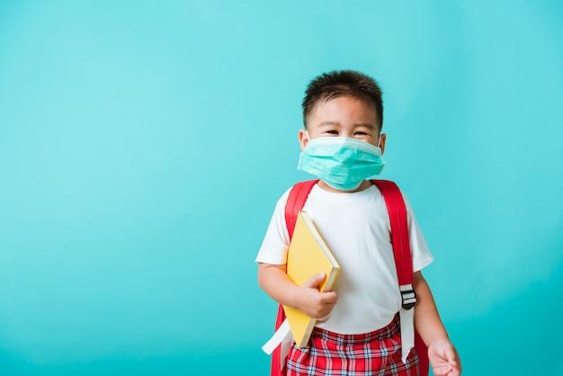 Portrait asiatique petit enfant garçon maternelle porter un masque protecteur et un sac d'école tenir le livre avant d'aller à l'école