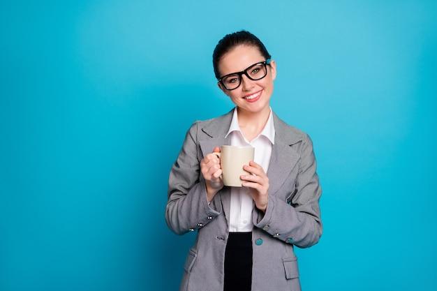 Portrait de l'assistant du chef de la direction positif tenir latte aromatique porter une veste de blazer de costume gris isolé sur fond de couleur bleu