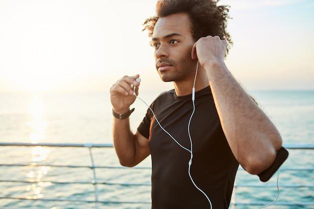 Portrait d'athlète afro-américain portant des écouteurs blancs, se prépare pour le jogging. courir au lever du soleil derrière la mer. concept de mode de vie sain