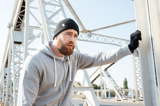 Portrait d'un athlète barbu ayant une pause après l'entraînement à l'extérieur